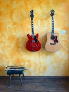 If you can drill some holes, hangers are a very cool option to display your guitars!
